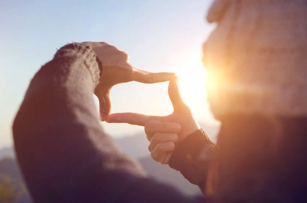 Close up of woman hands making frame gesture with sunrise on mou